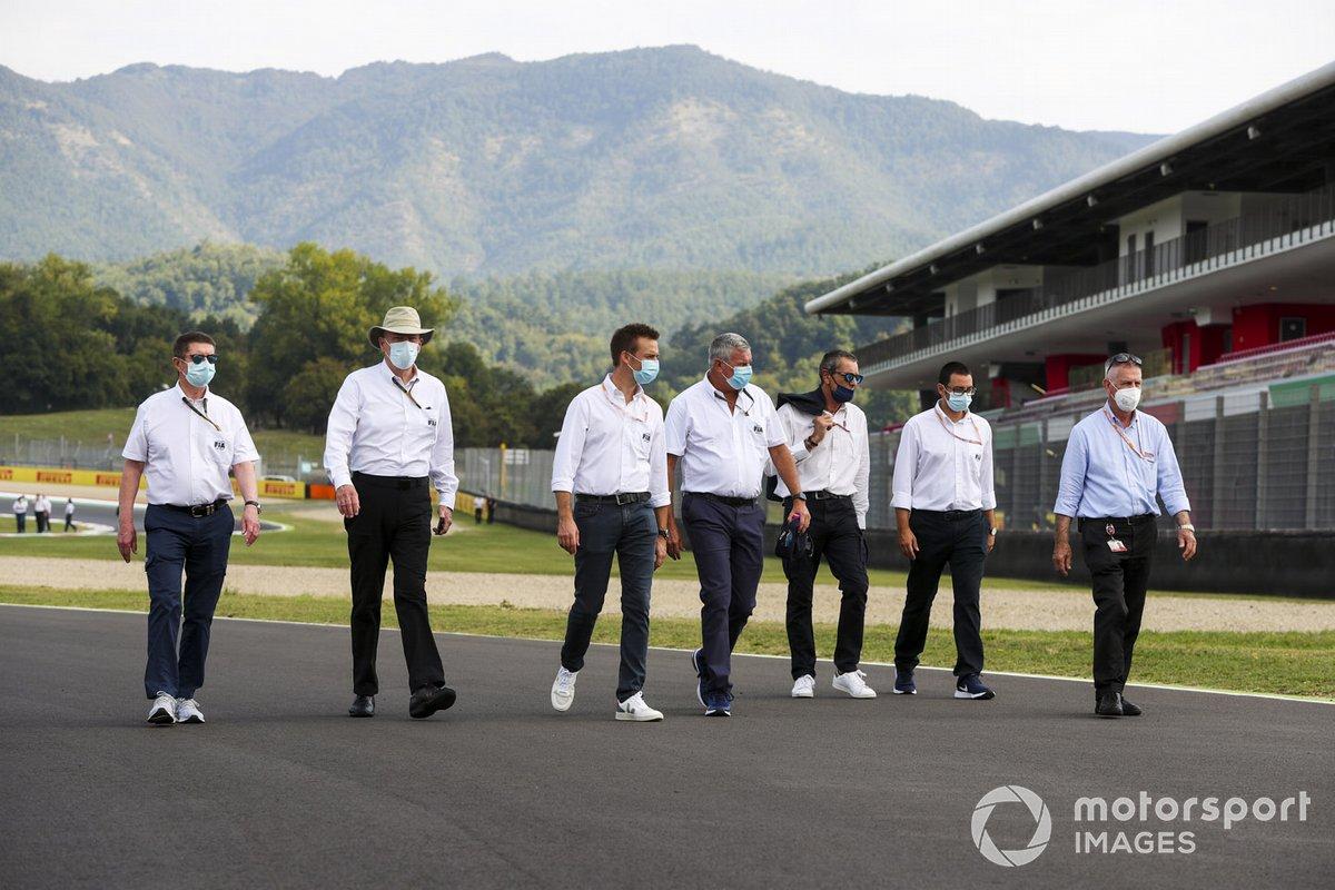 FIA members walk the track
