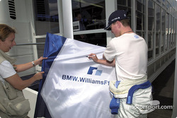 Ralf Schumacher signs an autograph for a fan