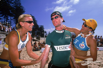 Eddie Irvine having suncream put on him by Australian Olympic Beach Volleyball gold medalists Kerry Pottharst and Natalie Cook for a game of Beach Volleyball held on Manly Beach in Sydney