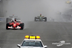 Rubens Barrichello leads the field behind the safety car