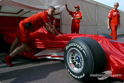 Ferrari team members push the car to technical inspection
