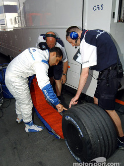 Juan Pablo Montoya checks tires