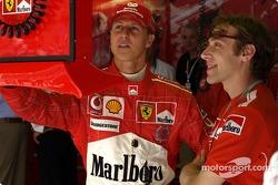 Michael Schumacher and Luca Badoer watch qualifying