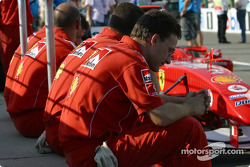 Ferrari team members wait for technical inspection