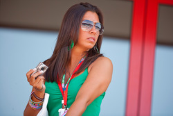 A girl above the pit lane watches the action