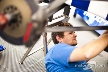 A mechanic works on the car of Dean Smith
