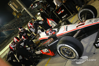 Crew works to repair suspension on the car of Will Power, Team Penske