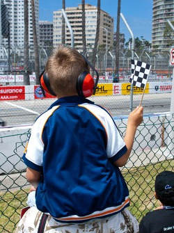 Young boy waves a checkered flag
