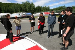 Sébastien Bourdais and Graham Rahal walk the track with Newman/Haas/Lanigan Racing crew members