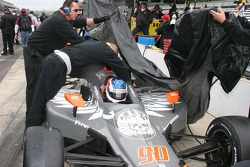 Townsend Bell's crew prepare to cover the car during the rain