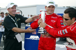 Second place qualifier Helio Castroneves jokingly tries to take away the MBNA Pole trophy from teammate Gil de Ferran