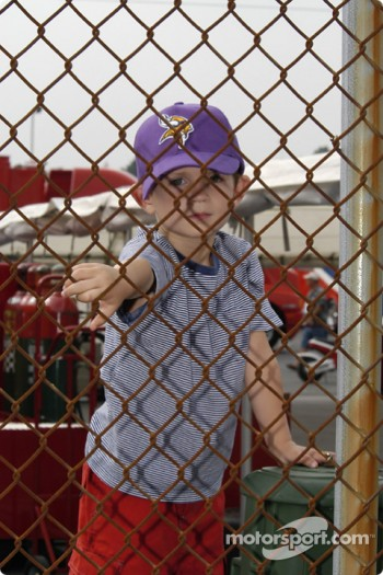 A young fans climbs the fence for a better view