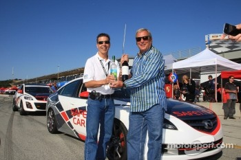 Scott Pruett gives Fuzzy Zoellera a bottle of wine from his own vineyard