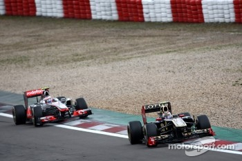 Vitaly Petrov, Lotus Renault GP leads Jenson Button, McLaren Mercedes