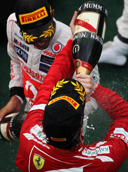 Race winner Fernando Alonso, Ferrari celebrates with the champagne with third placed Lewis Hamilton, McLaren on the podium