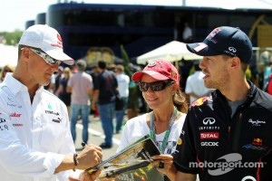 Michael Schumacher, Mercedes AMG F1 and Sebastian Vettel, Red Bull Racing with a fan
