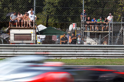 Jenson Button, McLaren passes fans on makeshift grandstands