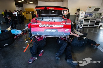 Stewart-Haas Racing Chevrolet crew members work on the wrecked car of Ryan Newman