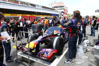 Red Bull Racing mechanic on the grid has his photo taken by a Lotus F1 Team mechanic