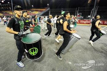 A drum band plays as fans walk the circuit