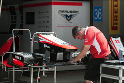 Marussia F1 Team MR02 front wing prepared in the pits by a mechanic