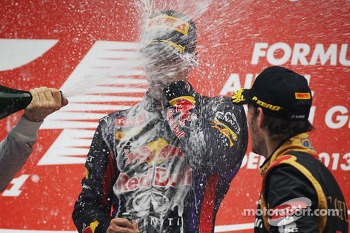 Race winner and World Champion Sebastian Vettel, Red Bull Racing celebrates on the podium with Romain Grosjean, Lotus F1 Team