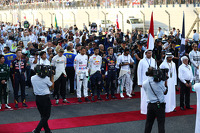 The drivers observe the anthem on the grid