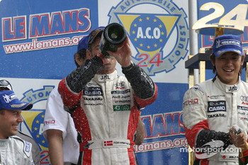 LM P1 podium: Tom Kristensen drinks some champagne, finally