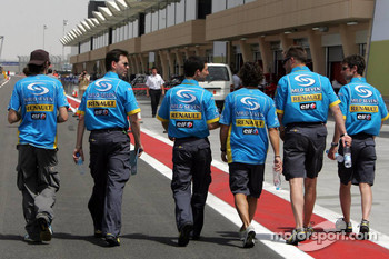 Fernando Alonso and Renault F1 team members walk the pitlane