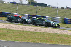 The Aston Martins race each other