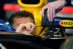 David Coulthard checks some measurements on his wing mirror