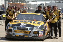 The DeWalt Ford Fusion is pushed through the garage area by the Roush Racing crew