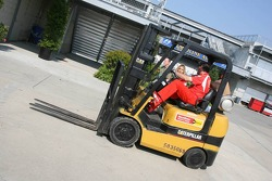A Ferrari team member drives a forklift truck in the pitlane