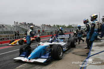Paul Tracy exits his pit while Sébastien Bourdais passes by