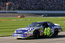 Jimmie Johnson exits pit road as Tony Stewart crosses the finish line to win the NASCAR Nextel Cup Series Banquet 400
