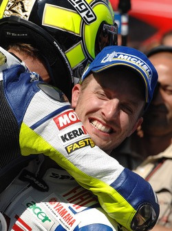 Race winner Valentino Rossi celebrates with Colin Edwards