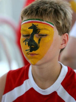 A young fan gets his faced painted with the Scuderia Ferrari badge