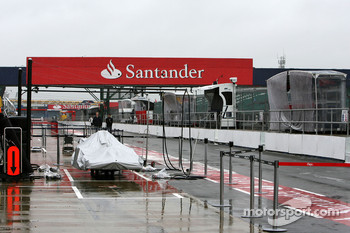 Cars stand in a wet pitlane