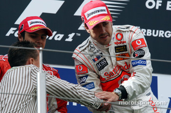 Podium: race winner Fernando Alonso celebrates with Michael Schumacher