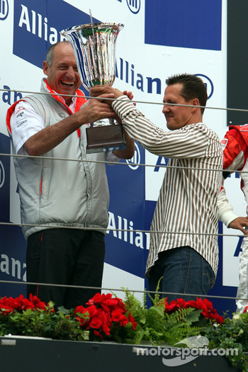 Michael Schumacher hands Ron Dennis the constructor trophy