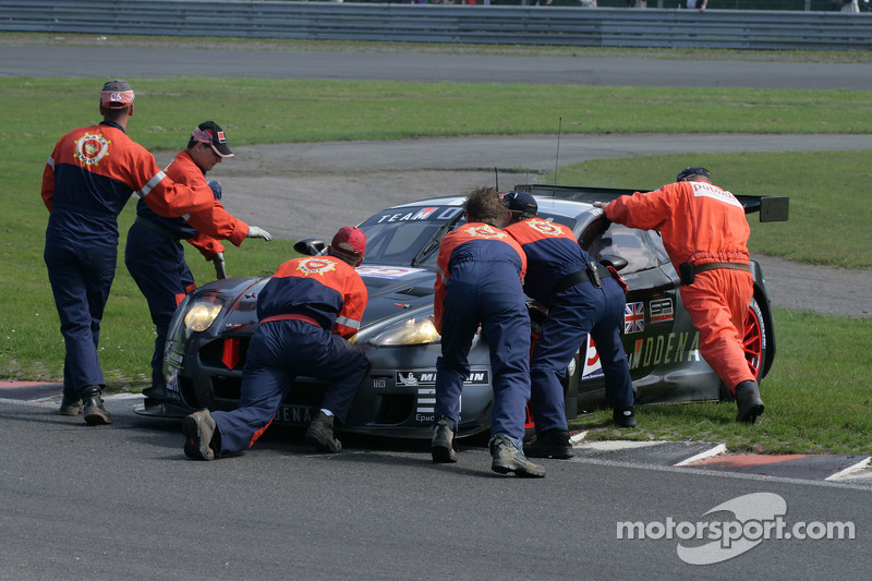 Marshalls attempt in vain to push #59 Team Modena Aston Martin DBR9: Antonio Garcia, Christian Fittipaldi backwards off the curb