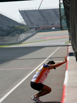 Nelson A. Piquet, Test Driver, Renault F1 Team, stretches against the wall on the pit straight
