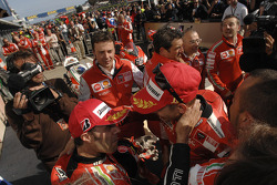 Race winner Casey Stoner celebrates with Loris Capirossi