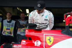 Lewis Hamilton, Mercedes AMG F1 W06 bekijkt de Ferrari SF15-T van Sebastian Vettel, Ferrari in parc ferme