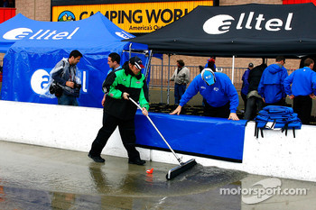 A crew member pushes standing water out of the pit box along pit road