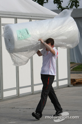 McLaren Mercedes, Team Member, carrying a package