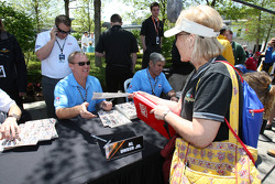 Race fans take the opportunity to get memorabilia signed by the Unser family