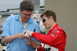 Ryan Briscoe signs an autograph