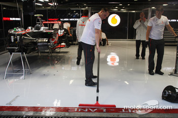 McLaren Mercedes, push water out of their garage after heavy rain