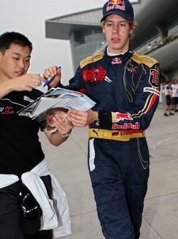 Sebastian Vettel gives an autograph